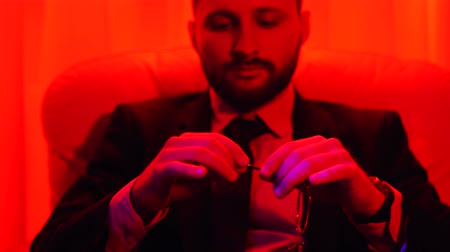 beardie : Portrait of a successful bearded businessman dressed in a business suit twisting glasses sitting in bright red light.