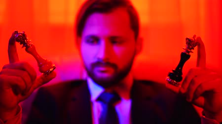 шах и мат : Portrait of a thoughtful successful businessman in a business suit holding a white and black chess figure in his arms sitting in the armchair in bright red light. Opportunity to choose in your hands