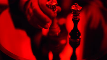 шах и мат : Male hand rearranging and dropping a chess figure standing on the table in bright red light.
