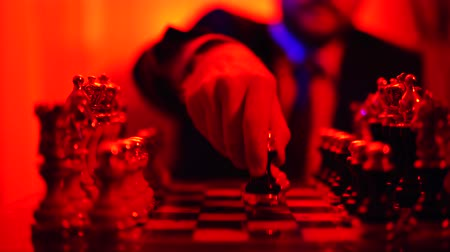 estratégico : Close-up of the hand of a man in a business suit sitting on a blurred background playing chess. Stock Footage