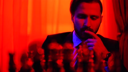 шах и мат : Thoughtful businessman in a business suit sitting on a blurred background pondering over strategy playing chess. Shooting in bright red light. Стоковые видеозаписи