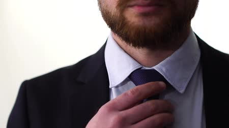 строгий : Confidence man in a shirt with a tie putting on a jacket and adjusting tie closeup. Стоковые видеозаписи