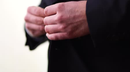 tutturma : Buttoning a jacket. Stylish man in a suit fastening buttons on his jacket preparing to go out. Close up