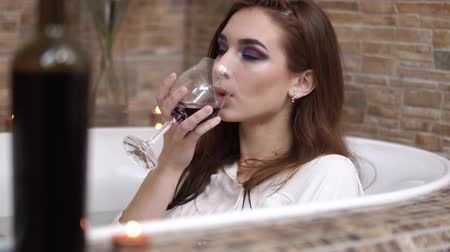 dinlenmek : Portrait of cute young woman in white shirt with wine glass taking a bath. Sensual girl enjoying in the bathroom with burning candles. Bottle in the foreground blurred.