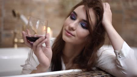 fürdés : Dreamy young woman in white shirt drinks red wine from high glass sitting in luxary bath and smiles close up. Stock mozgókép