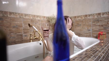 bor : Portrait of upset girl taking a bath with bright makeup in a white shirt with wine glass. Bottles in the foreground on the edge of the bath.