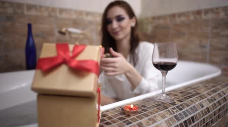 telefon : Young woman opens present box an gets small pink rose taking a bath