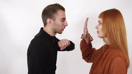insult : Angry aggressive man want to beat his woman, he is yelling. Woman raise hand showing him to stop violence