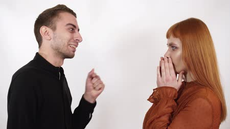 insult : Angry agressive man yelling at his beautiful girlfriend with long red hair. Woman close her face and ears, she can not listen this bad words. Stock Footage