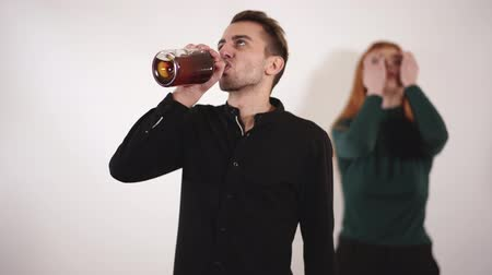 bağırıyor : Aggressive drank man with bouttle of alcohol drinking from a bottle and upset young woman with long red hair yelling and crying.