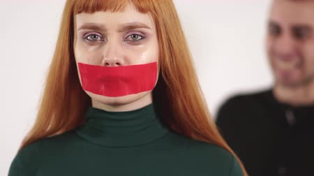 humiliation : Portrait of young woman with taped mouth is silent while aggressive angry man are screaming and yelling at female.