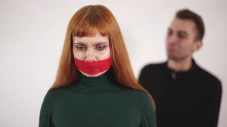 gritante : Portrait of young woman with taped mouth is silent while aggressive angry man are screaming and yelling at female.