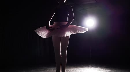 estatuária : Graceful girl practicing ballet in the studio. Silhouette of ballerina in spotlight on black background. Slow motion.