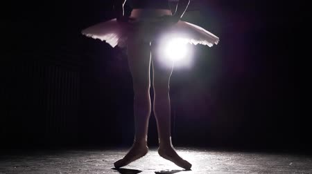 sznurek : Ballet dancer practicing exercises on dark studio. Silhouette of ballerina in spotlight on black background in studio. Ballerina wearing tutu and pointe shoes. Slow motion. Wideo