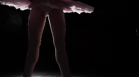 nőiesség : Beautiful leg of young ballerina in pointe shoes. Ballet practice. Beautiful slim graceful legs of ballet dancer on black background.