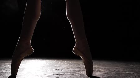 sznurek : Beautiful leg in pointe shoes on black background. Ballet practice. Slow motion.