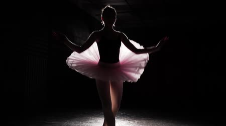 estatuária : Ballerina performs fouette turns in spotlight on black background in training room. Female ballet dancer wearing tutu and pointe shoes. Slow motion.