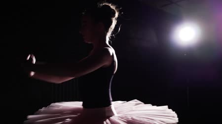 hangar : Young and graceful ballerina dancing on her pointe ballet shoes in spotlight on black background in studio.. Woman shows classic ballet pas wearing tutu and pointe shoes. Slow motion. Stock Footage