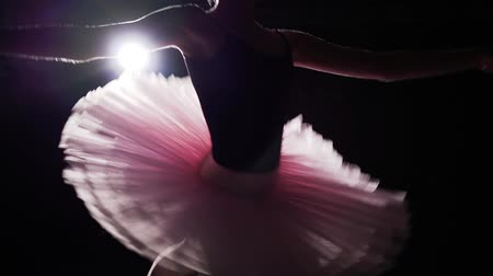 比喩的な : Graceful young flexible ballerina dancing on her pointe ballet shoes in spotlight on black background in studio. Ballet dancer shows classic ballet pas wearing tutu and pointe shoes. Slow motion.