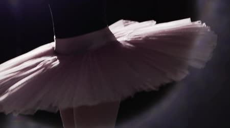 sznurek : Beautiful young ballerina dancing on her pointe ballet shoes on black background in studio. Ballet dancer shows classic ballet pas wearing tutu and pointe shoes. Slow motion.