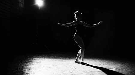 estatuária : Professional graceful flexible ballerina dancing on her pointe ballet shoes in spotlight on black background in studio. Black and white shot. Slow motion. Stock Footage