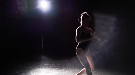 güzel sanatlar : Professional flexible ballerina dancing on her pointe ballet shoes in spotlight on black background in studio. Ballet dancer shows classic ballet pas wearing tutu and pointe shoes. Slow motion. Stok Video