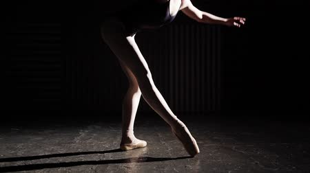 estatuária : Professional graceful flexible ballerina standing on her pointe ballet shoes in spotlight on black background in studio. Slow motion.