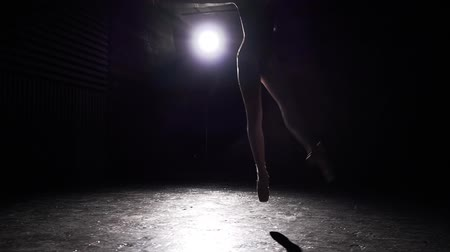 hangar : Young professional graceful flexible ballerina dancing on her pointe ballet shoes in spotlight on black background in studio. Slow motion. Stock Footage