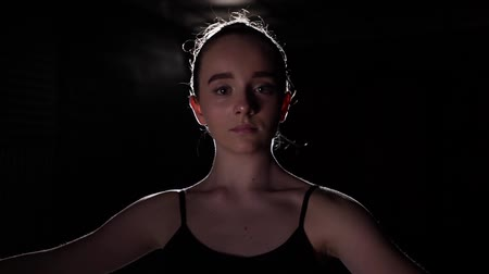 floodlight : Portrait professional young ballerina standing in spotlight on black background in studio. Ballet dancer shows classic ballet pas. Slow motion.