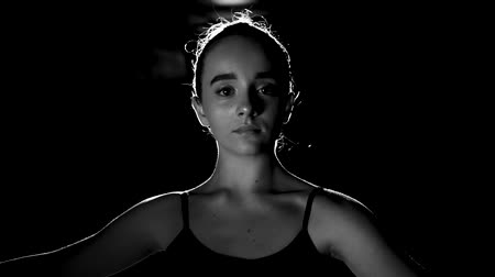 estatuária : Portrait professional young ballerina standing in spotlight on black background in studio. Ballet dancer shows classic ballet pas. Black and white shot. Slow motion.