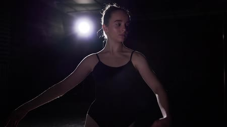 estatuária : Portrait professional cute ballet dancer standing in spotlight on black background in studio. Ballerina shows classic ballet pas. Slow motion. Stock Footage