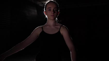 比喩的な : Portrait cute ballet dancer standing in spotlight on black background in studio. Ballerina shows classic ballet pas. Slow motion.