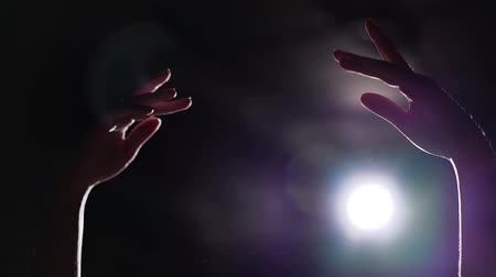 estatuária : Closeup of female hands raised up in spotlight on black background Stock Footage
