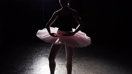 floodlight : Graceful flexible ballerina dancing on her pointe ballet shoes in spotlight on black background in studio. Girl shows classic ballet pas wearing tutu and pointe shoes.