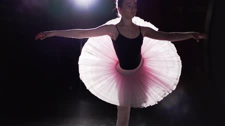 sznurek : Graceful flexible girl dancing on her pointe ballet shoes in spotlight on black background in studio. Professional ballerina shows classic ballet pas wearing tutu and pointe shoes.