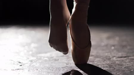 toes : Close up of female legs standing in pose in spotlight on black background in studio. One feet in pointe and another feet without shoe on the toes.