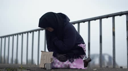 poorness : Adult homeless woman with sits on the bridge in cold windy grey weather asking for alms and help and coughing