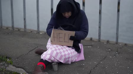 poorness : Adult homeless woman sits on the bridge in cold windy grey weather asking for alms and help and writs something on carton
