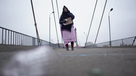 poorness : Adult homeless woman stay on the bridge near the river port in cold windy grey weather asking for help and begging money