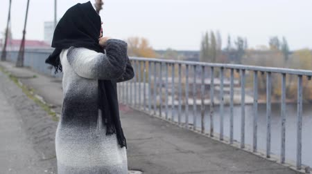 poorness : Adult woman walks across the bridge in cold windy grey weather and stopped to wear scarf on the head