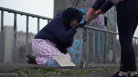 alms : Adult homeless woman with outstretched hand sits on the bridge in cold windy grey weather asking for alms and help and one woman stopped to put coins