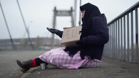 poorness : Old woman begging on the street. Homeless beggar asking for help.