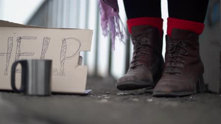 poorness : Feet moving in leather brown shoes on the street becouse of the cold next to a sign on carton of help. Close up