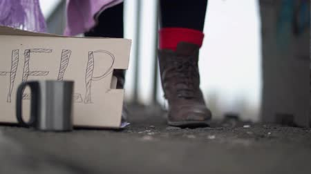 poorness : Close up of feet moving in leather brown shoes on the street becouse of the cold next to a sign on carton of help.