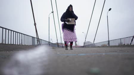 poorness : Elderly homeless woman stay on the bridge near the river port in cold windy grey weather asking for help and begging money Stock Footage