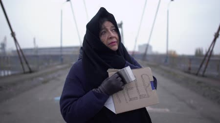 alms : Portrait of adult sad homeless woman stay on the bridge in cold windy grey weather asking for alms and help Stock Footage