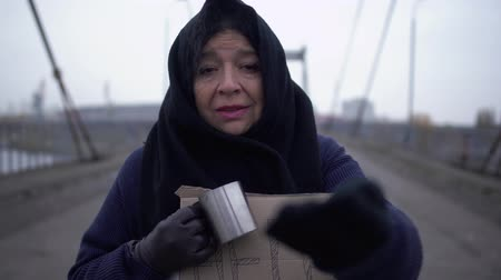 alms : Portrait of adult sad homeless stay on the bridge in cold windy grey weather asking for alms and charity