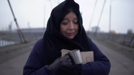 alms : Portrait of adult sad homeless woman stay on the bridge in cold windy grey weather asking for alms and help and one woman stopped to put coins