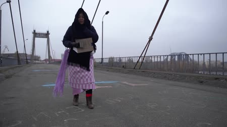 poorness : Adult homeless woman go along the bridge near the river port in cold windy grey weather asking for help and begging money Stock Footage
