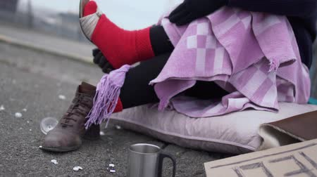poorness : Homeless women wear sandals putting them on wool socks while sitting on cardboard outdoors. Stock Footage